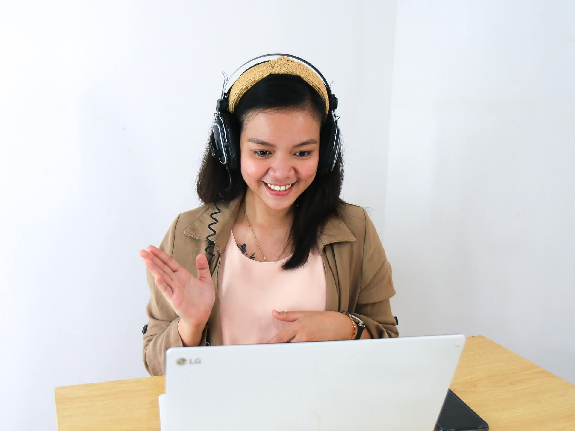 girl waving in front of laptop
