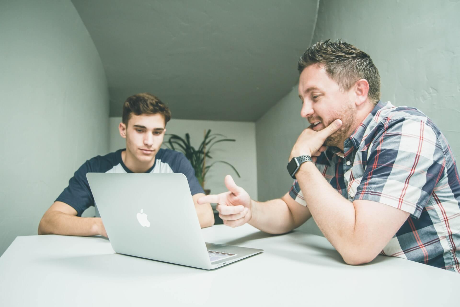 Two men talking around laptop