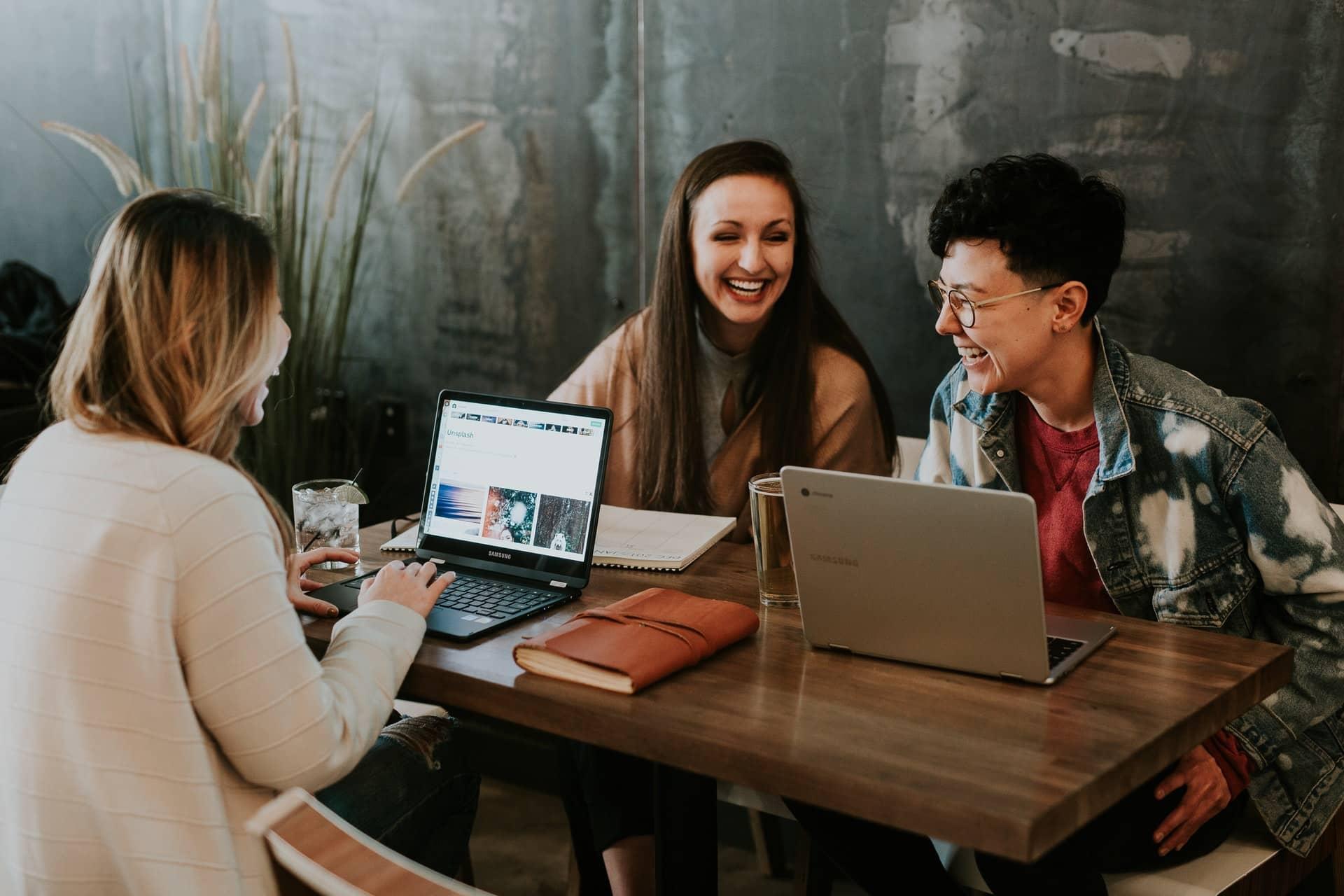 women laughing around laptops