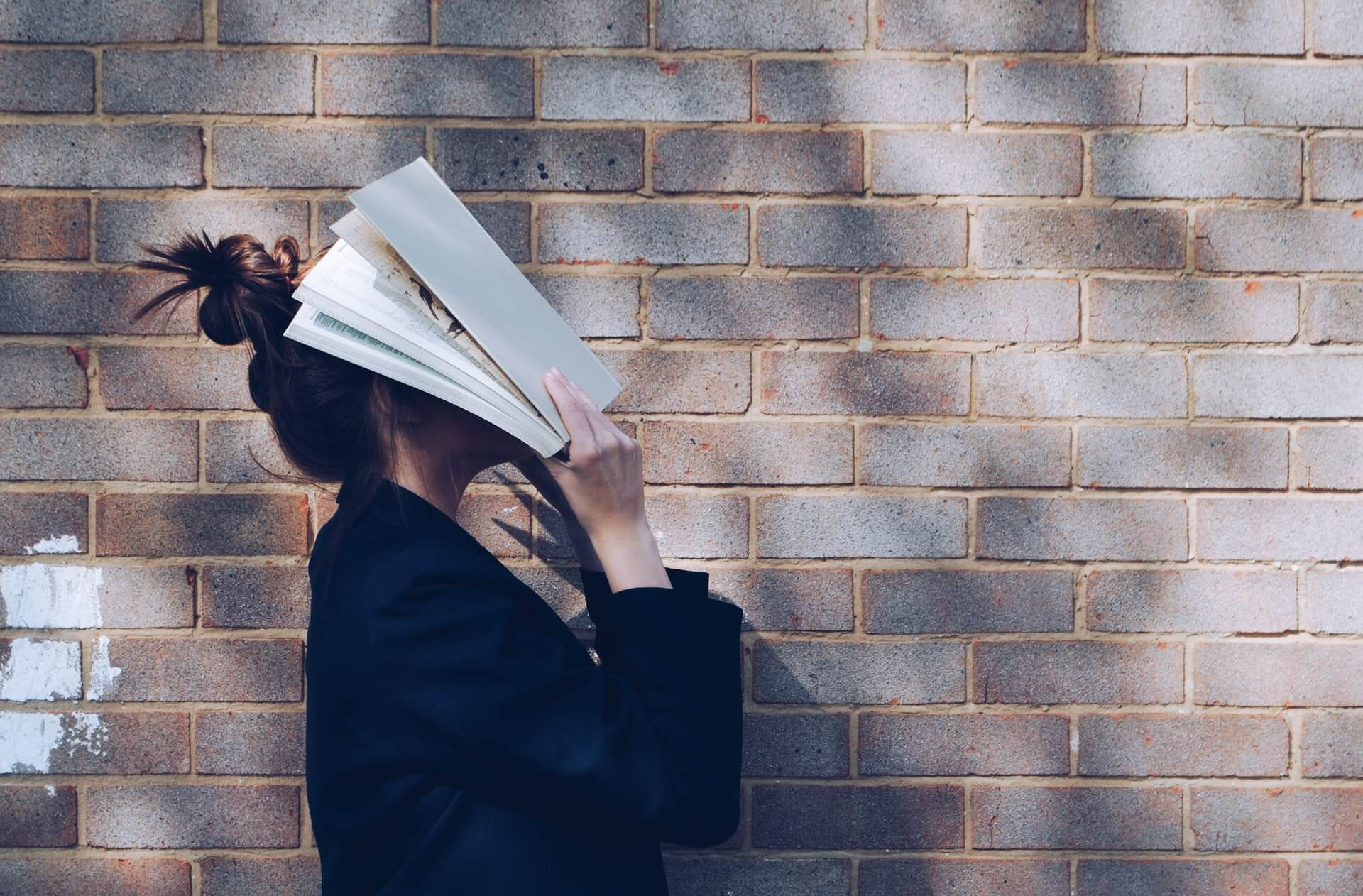 woman covering her face with a textbook